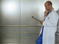 Mature male doctor in lift, looking at clipboard, side view