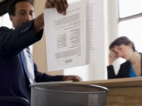 Businessman throwing away report into trash